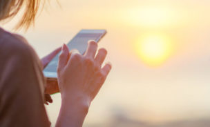 Someone uses their phone whilst watching a sunset